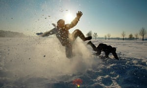 Two kids falling around and kicking up snow