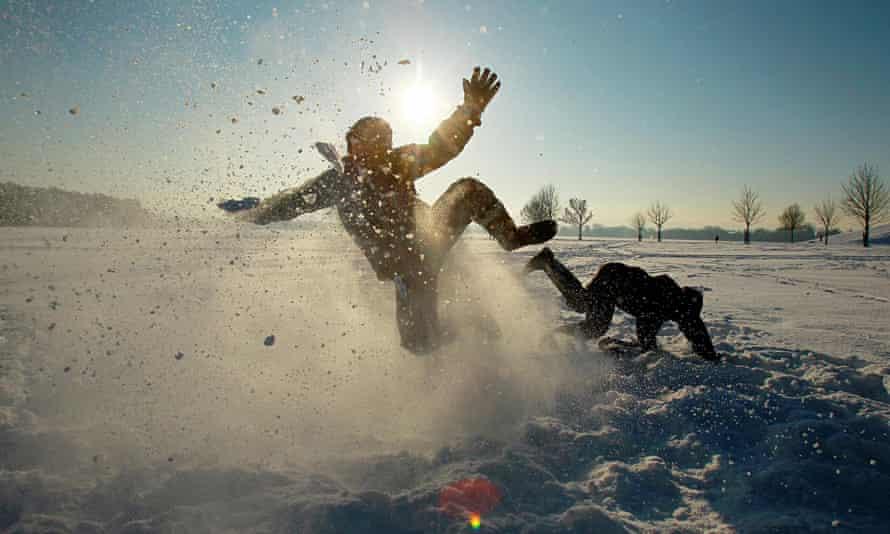 Two kids falling around and kicking up snow