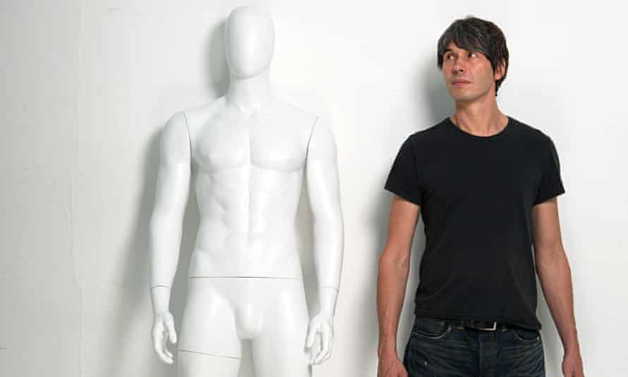Physicist Brian Cox in a T-shirt looking at a shop mannequin