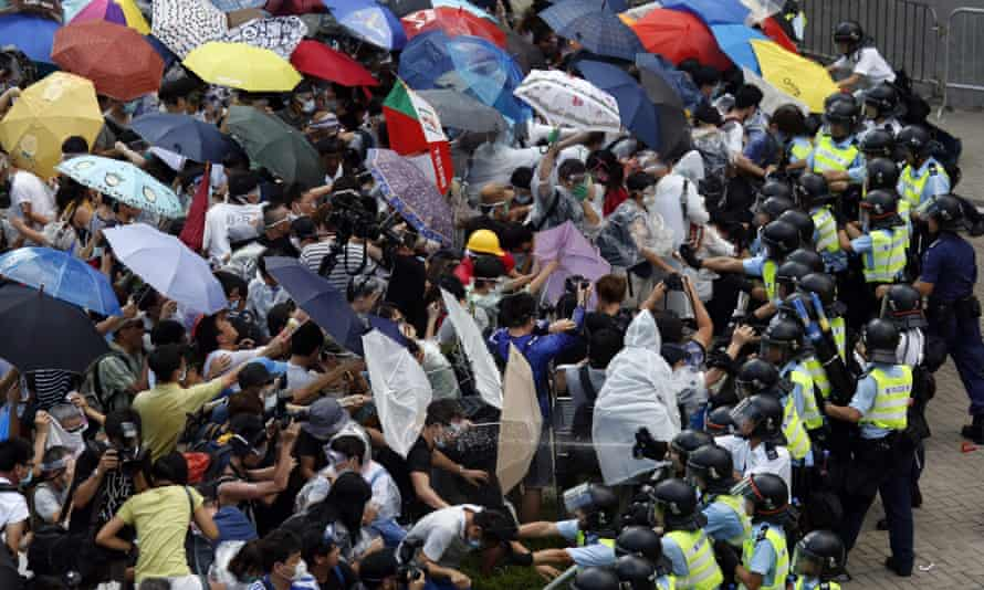 Protesters take cover from pepper spray with umbrellas as riot police clash with them in Hong Kong