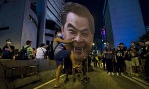 A protester hits a cutout of Hong Kong chief executive Leung Chun-ying, which had been given fangs.
