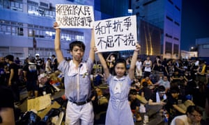 High-school students still in their uniforms hold signs during a protest outside the headquarters of the legislative council in Hong Kong.