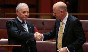 South Australian family first senator Bob Day is congratulated by  Senator David Leyonhjelm.