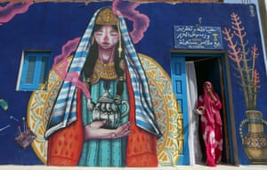 A seamstress stands at the entrance of her workshop decorated by Spanish artist Malakkai
