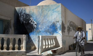 A man rides past a mural by French artist C215 decorating a wall