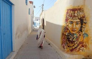 A Tunisian woman walks past a mural by Spanish artist Btoy