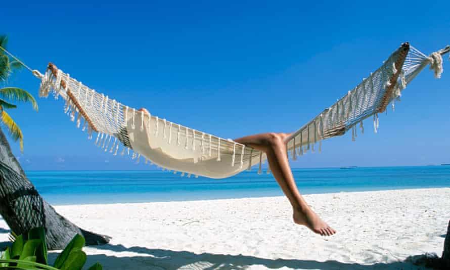 Woman lies in hammock on beach