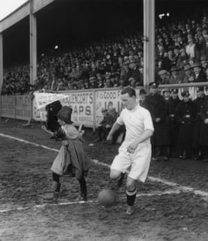 Mascot Miss Waters leads out the Swansea City team before an FA Cup sixth round match against Arsenal at the Vetch Field, Swansea in March 1926. Waters' pennant reads: 'Play Up The Swans'.