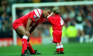 Liverpool's John Barnes takes time out to have a kindly word with the tearful young mascot in 1990.