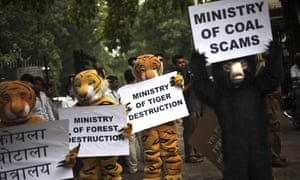 Greenpeace activists dressed as wild animals hold placards during a protest outside the office of the Indian coal minister