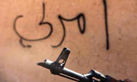 A Shia militia fighter holds a gun