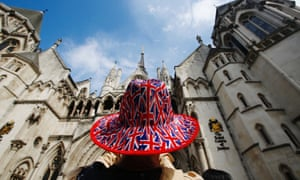 A man wears a hat printed with union flags outside the royal courts of justice in London.