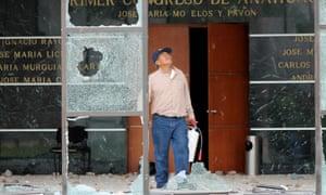 A civil servant surveys damage at the Guerrero state congress building in Chilpancingo.