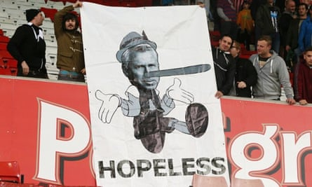 Newcastle United fans hold up a banner portraying Alan Pardew as Pinocchio