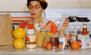 1960s woman in kitchen with glasses, shopping list and tins of food