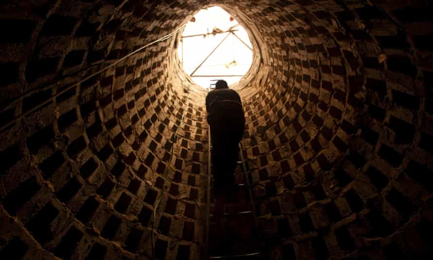 A Palestinian climbs out of a tunnel