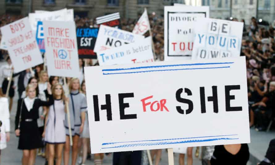 A model holds a sign reading He for She on the catwalk