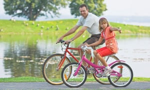 Father and daughter cycling together