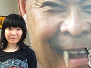 Timmie Yu posed next to a picture of fake-fanged chief executive CY Leung.