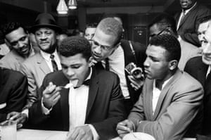 This is a scene from a party after Clay beat Sonny Liston for the heavyweight title. Such is the power of his celebrity, the assembled crowd are jostling around him simply to watch him eat. The proximity of Malcolm X to Clay serves as a neat metaphor for the closeness of their relationship at that time.