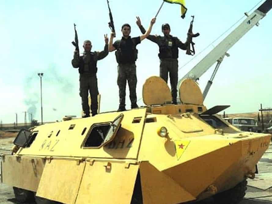 Kurdish fighters on yellow APC