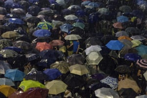 Pro-democracy protestors use umbrellas to shield themselves from heavy rain in Hong Kong on September 30, 2014.