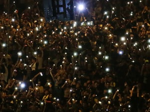 "Protesters chant ""Jiayou! Jiayou!""   or ""Keep it up!""   while waving their cellphones with the LED flashlights sparkling in the dark as they gather on the streets near the government headquarters, Wednesday, Oct. 1, 2014 in Hong Kong."