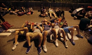 Student protesters rest as thousands occupy a main thoroughfare in Hong Kong, late Tuesday, Sept. 30, 2014.