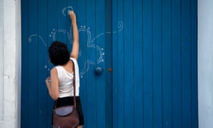 Woman drawing on door with chalk