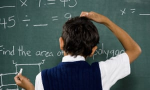 boy at chalkboard doing math formulas and scratching head