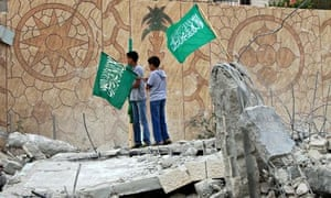 Palestinians raise Hamas flags at what remains of the house of Hussam Qawasmeh