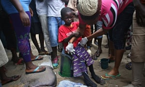 Neighbours dress a sick Saah Exco, 10, after bathing him in Monrovia's West Point slum, Liberia.