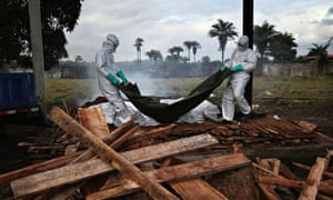 A burial team puts bodies of Ebola victims on to a funeral pyre in Marshall, Liberia.