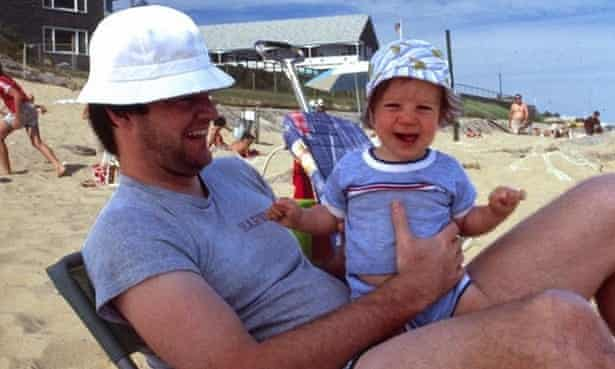 a man holding a baby boy whilst sitting on the beach