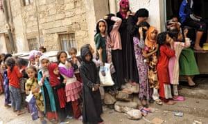 Yemeni children queue at a charity centre