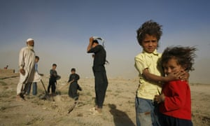 Afghan refugees returning from Iran and Pakistan are given small plots of land to build a new home. A family stands on a barren, dusty plain near Bagram, Afghanistan, August 5, 2007.