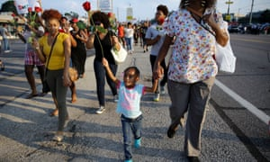 A girl holds a rose as she marches in Ferguson, Missouri