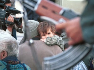 An Afghan child looks on as Iran's police stopped a group of illegal Afghan refugees at Kooleh Sangi in Baluchistan province in Iran, October 16, 2001.