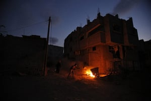 20 Photos: A Palestinian man lights a fire in an area heavily shelled by Israel