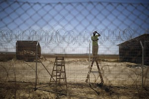 20 Photos: An Israeli worker repairs a fence damaged by a tank in Kibbutz Nahal Oz