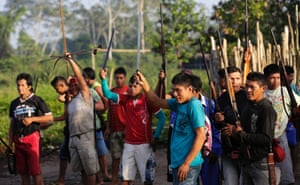 Ka'apor Indian warriors gesture to members of their tribe as they depart on a jungle expedition to search for and expel loggers from the Alto Turiacu Indian territory, in the village of Waxiguy Renda near the Centro do Guilherme municipality in the northeast of Maranhao state in the Amazon basin, August 7, 2014.