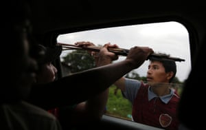 Ka'apor Indians hand bows and arrows to tribal warriors traveling by truck through their village of Ximborenda, on the way to search for and expel loggers from the Alto Turiacu Indian territory, near the Centro do Guilherme municipality in the northeast of Maranhao state in the Amazon basin, August 6, 2014.
