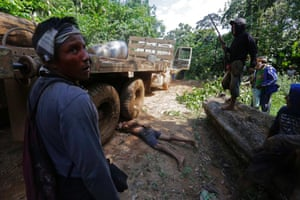 Ka'apor Indian warriors stand over a logger they tied up during a jungle expedition to search for and expel loggers from the Alto Turiacu Indian territory, near the Centro do Guilherme municipality in the northeast of Maranhao state in the Amazon basin, August 7, 2014.