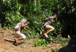 A Ka'apor Indian warrior (L) chases a logger who tried to escape after he was captured during a jungle expedition to search for and expel loggers from the Alto Turiacu Indian territory, near the Centro do Guilherme municipality in the northeast of Maranhao state in the Amazon basin, August 7, 2014.