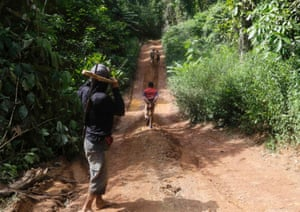 A Ka'apor Indian warrior (L) watches as loggers run off after being released after a jungle expedition to search for and expel them from the Alto Turiacu Indian territory, near the Centro do Guilherme municipality in the northeast of Maranhao state in the Amazon basin, August 7, 2014.