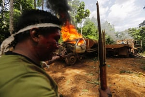 A Ka'apor Indian warrior stands near a burning logging truck during a jungle expedition to search for and expel loggers from the Alto Turiacu Indian territory, near the Centro do Guilherme municipality in the northeast of Maranhao state in the Amazon basin, August 7, 2014.