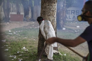 20 photos: A man hides behind a tree as riot police use teargas in Islamabad