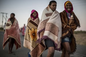 'Maidens' wrap themselves in blankets as they head to a ritual bath in a local river.