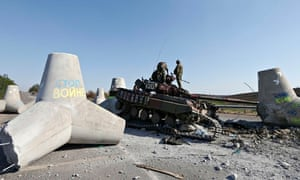 Ukrainian soldiers inspect a damaged tank on the outskirts of of Mariupol.