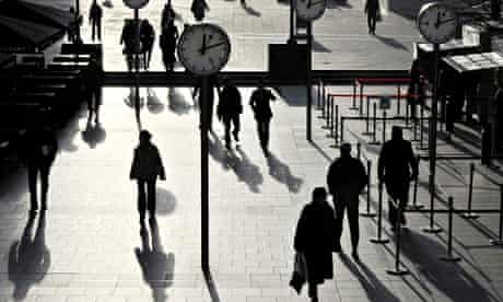 Workers walk past clocks in Canary Wharf